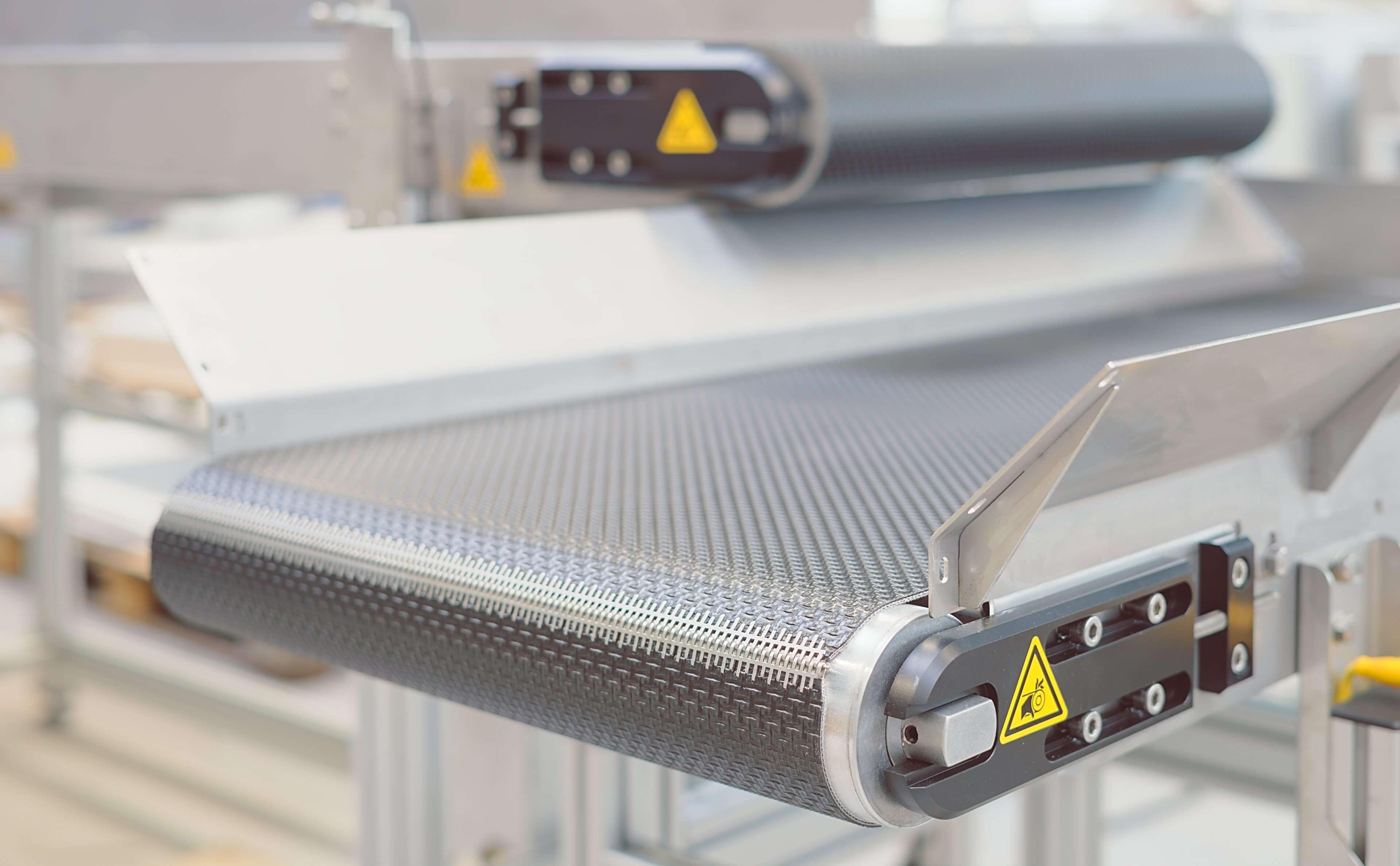 Foerderband MINITRANS H65 mit Seitenfuehrung, Not-Halt-Tasten und einem Frequenzumrichter zur Geschwindigkeitsregelung