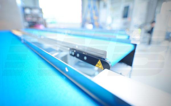 Förderband mit blauem Gurt und fester Seitenführung