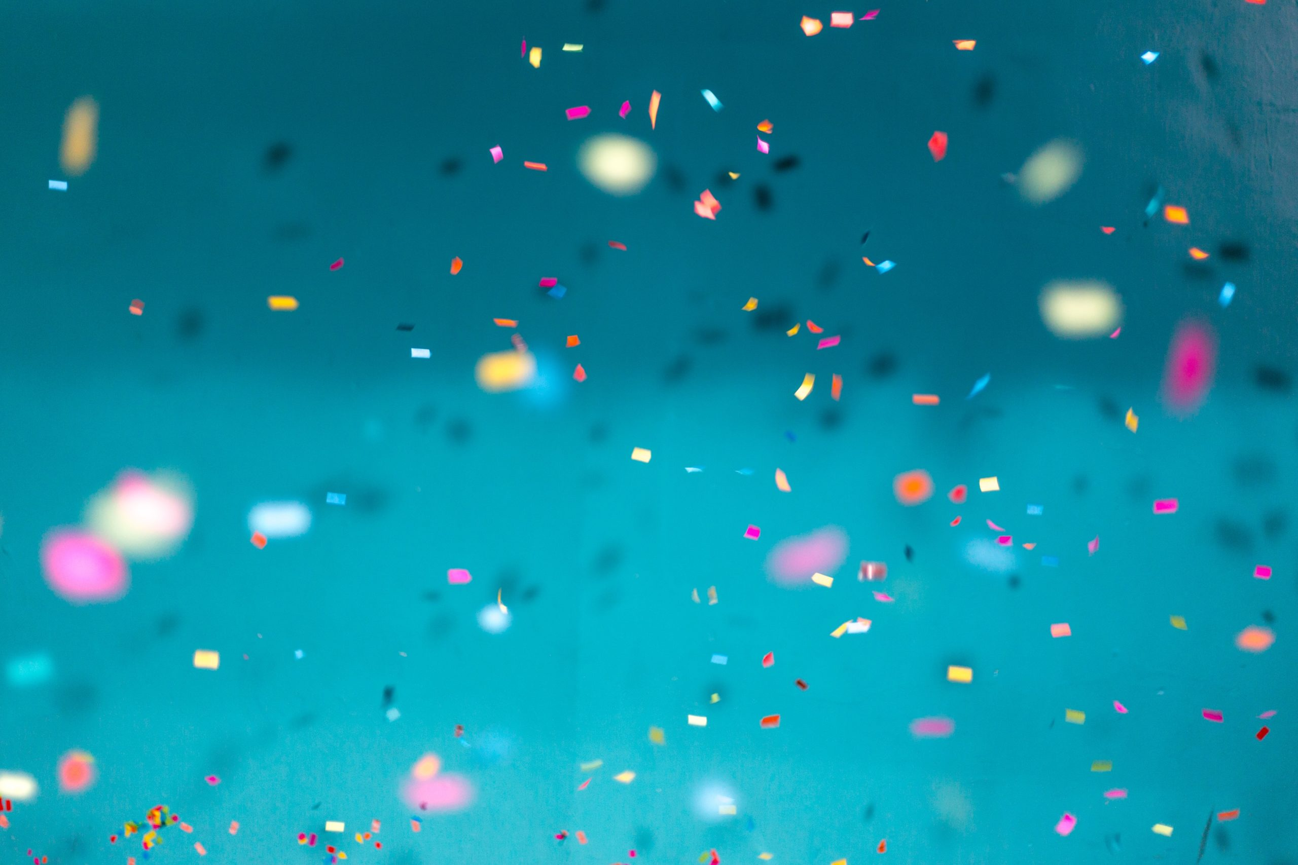 Colorful confetti falling down with a teal background